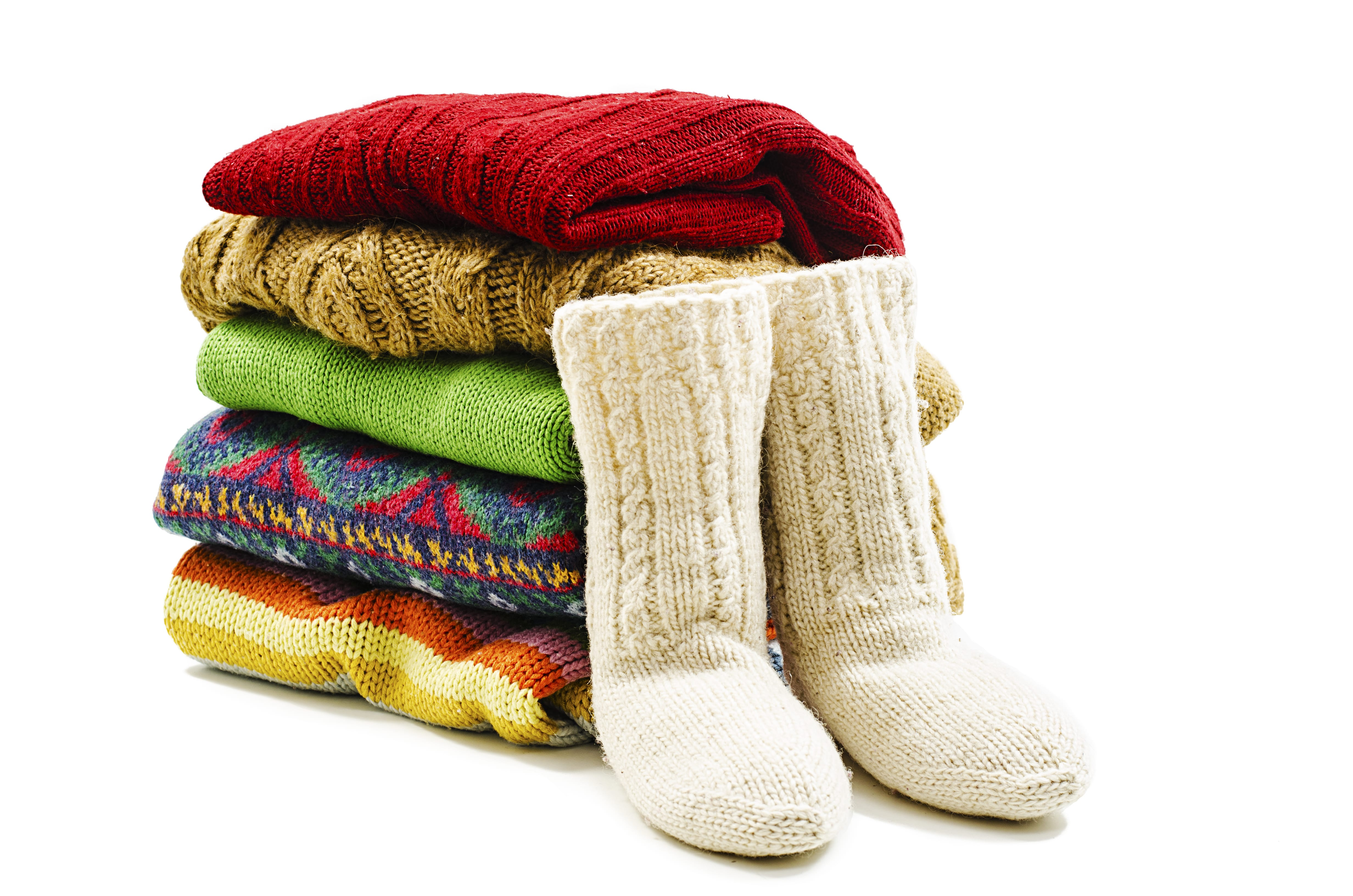A neat pile of colorful sweaters sit next to a pair of cozy wool slippers, ready to be prepped for winter storage.