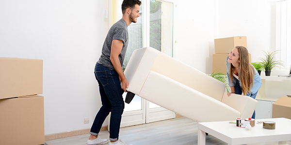 couple moving a couch in their new home
