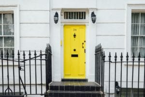 Adding curb appeal to a white home is easy with a contrasting yellow door.